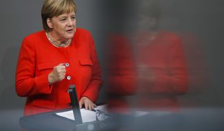 In this photo taken with a reflection in a window of the visitors tribune, German Chancellor Angela Merkel delivers her speech during a plenary session of the German parliament Bundestag about the budget 2019, in Berlin, Wednesday, Sept. 12, 2018. (AP Photo/Markus Schreiber)