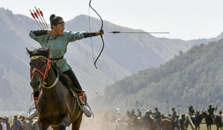 In this photo taken on Thursday, Sept. 6, 2018, a women releases an arrow during an archery competition during the Third Nomad Games, in Cholpon-Ata, 250 kilometers (156 miles) of Bishkek, Kyrgyzstan. The Central Asian nation of Kyrgyzstan held its biennial Nomad Games to promote and celebrate traditional sports of nomadic people. The week-long competition, which is held in a gorge near the picturesque Lake Issyk-Kul, feature traditional sports of nomad peoples such as horseback wrestling and goat polo.  (AP Photo/Vladimir Voronin)