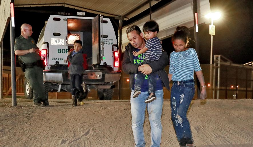 In this July 18, 2018 file photo, a Honduran man carries his 3-year-old son as his daughter and other son follow to a transport vehicle after being detained by U.S. Customs and Border Patrol agents in San Luis, Ariz. (AP Photo/Matt York, File) **FILE**
