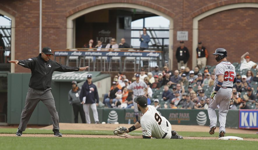 Atlanta Braves' Tyler Flowers makes it safely to first base as San Francisco Giants first baseman Brandon Belt (9) looks for the ruling from umpire Jeremie Rehak during the ninth inning of a baseball game Wednesday, Sept. 12, 2018, in San Francisco. The Braves' Charlie Culberson scored a run on the play. Atlanta won the game 2-1. (AP Photo/Eric Risberg)