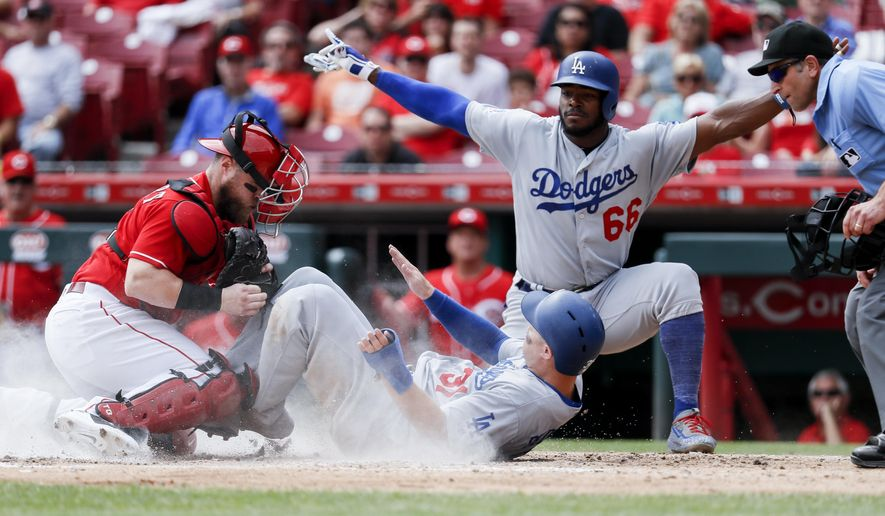 Los Angeles Dodgers' Joc Pederson (31) scores against Cincinnati Reds catcher Tucker Barnhart, left, as Yasiel Puig (66) reacts in the fifth inning of a baseball game, Wednesday, Sept. 12, 2018, in Cincinnati. (AP Photo/John Minchillo)