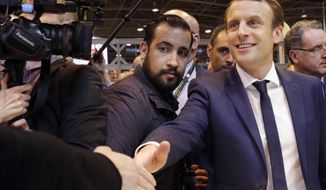 FILE - In this March 1, 2017 file photo, French presidential candidate Emmanuel Macron, front right, flanked by his bodyguard, Alexandre Benalla, centre left, in Paris. Former security aide to French President Emmanuel Macron, Alexandre Benalla, who set off a political scandal after being videotaped beating up a protester said Wednesday Sept. 12, 2018, that he will appear before a Senate inquiry commission as requested, because he has no choice. (AP Photo/Christophe Ena, FILE)