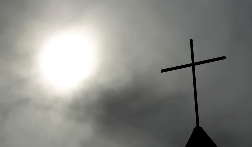 In this April 8, 2010 file photo a cross sits on top of a church in Berlin, Germany.  (AP Photo/Markus Schreiber, File) **FILE**