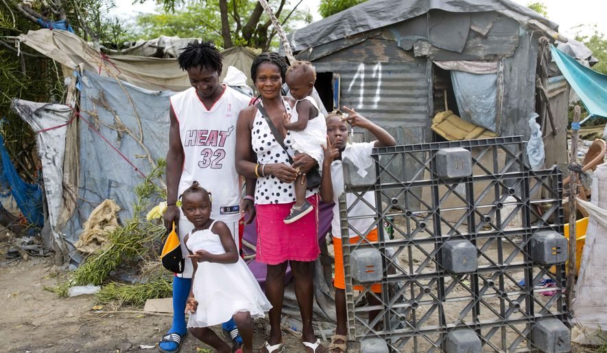 In this Aug. 29, 2018 photo, Changlair Aristide stands with his wife Violene Mareus and children outside their home near the Truitier landfill where Aristide scavenges for valuables to use or sell in the Cite Soleil slum of Port-au-Prince, Haiti, before Aristide leaves to play soccer with a group of friends. Mareus said she hopes to move to a nice home one day in which she doesn't have to hold up tarps when it rains. (AP Photo/Dieu Nalio Chery)