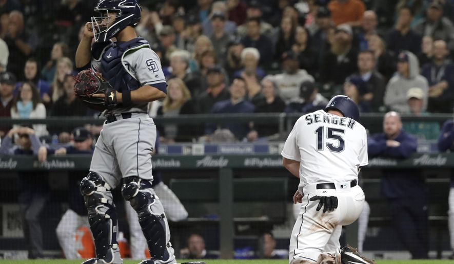 Seattle Mariners' Kyle Seager kneels at the plate after he was tagged out at home by San Diego Padres catcher Francisco Mejia, left, on a fielders choice play during the seventh inning of a baseball game, Tuesday, Sept. 11, 2018, in Seattle. (AP Photo/Ted S. Warren)