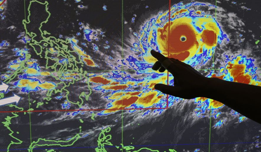 """Filipino forecaster Meno Mendoza illustrates the path of Typhoon Mangkhut, locally named """"Typhoon Ompong"""" as it approaches the Philippines with sustained winds of 205 kilometers per hour (127 miles per hour) and gusts of up to 255 kph (158 mph), at the Philippine Atmospheric, Geophysical and Astronomical Services Administration in metropolitan Manila, Philippines on Wednesday, Sept. 12, 2018. Philippine officials say they plan to evacuate thousands of villagers, shut down schools and offices and scramble to harvest rice and corn as the most powerful typhoon so far this year menacingly roars toward the country's north. (AP Photo/Aaron Favila)"""
