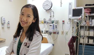 In this Aug. 14, 2012, file photo, Dr. Leana Wen stands in the emergency department at Brigham and Women's Hospital in Boston, during her medical residency. (AP Photo/Steven Senne) ** FILE **