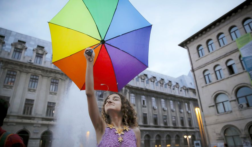 "A girl takes part in a gay rights activists protest against proposed changes to the constitution that would prevent future recognition of same-sex marriages, in Bucharest, Romania, Tuesday, Sept. 11, 2018. Romanian Senators on Tuesday approved a measure that would pave the way for the constitution, which currently states that marriage is a union between ""spouses"", to be changed to explicitly state that marriage is a union of a man and a woman. (AP Photo/Vadim Ghirda)"