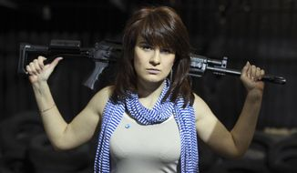 In this Sunday, April 22, 2012, file photo, Maria Butina, a gun-rights activist, poses for a photo at a shooting range in Moscow, Russia. (AP Photo/Pavel Ptitsin, File)