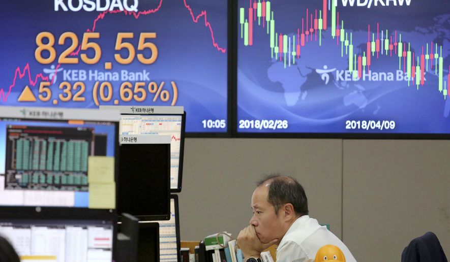 A currency trader watches monitors at the foreign exchange dealing room of the KEB Hana Bank headquarters in Seoul, South Korea, Wednesday, Sept. 12, 2018. Asian shares fell on Wednesday as China delayed issuing licenses to American businesses hoping to operate in the country, as the threat of more trade tariffs from Washington loomed. (AP Photo/Ahn Young-joon)
