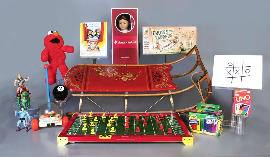 This Aug. 23, 2018 photo provided by The National Toy Hall of Fame in Rochester, N.Y., shows the 12 finalists for the class of 2018. The winners will be inducted on Nov. 8, 2018. Starting with the back row from left are Tickle Me Elmo, pinball, American Girl dolls, and Chutes & Ladders. In the center row from left are sled, and tic-tac-toe. In the front row from left are Masters of the Universe, Fisher-Price Corn Popper, Magic 8 Ball, Tudor Electric Football, chalk and Uno. (National Toy Hall of Fame via AP)