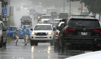 A couple walks in a rainstorm amid heavy traffic in Paia, Hawaii, on Tuesday, Sept. 11, 2018, as Tropical Storm Olivia marched closer to Maui. Olivia was expected to pass directly over Maui on Tuesday night into Wednesday morning. (Matthew Thayer/The News via AP)