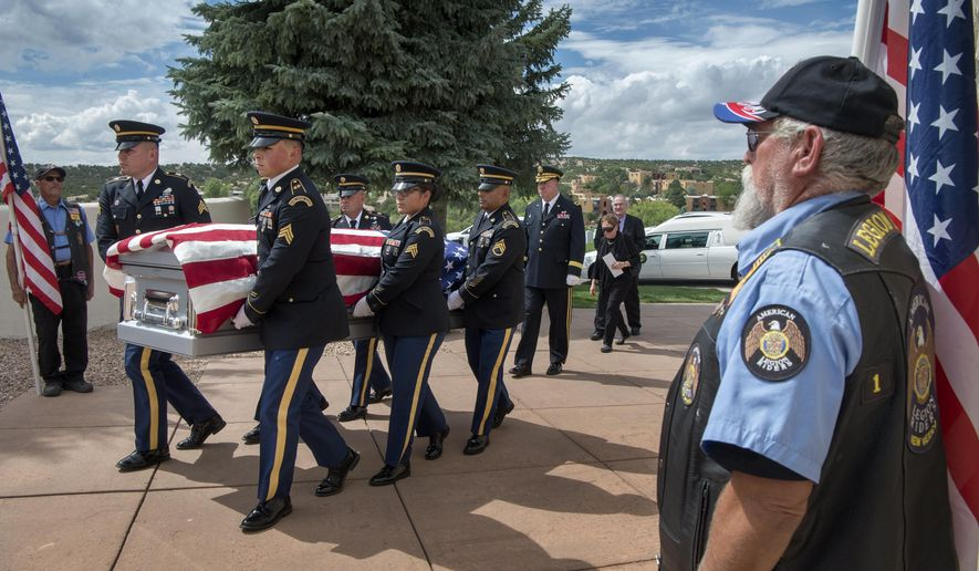 In a Wednesday August 22, 2018 photo, pallbearers with the New Mexico National Guard, followed by Brig. Gen. Tom Bump, carry the body of WWII Army Air Forces Sgt. Alfonso Duran to his burial service at the Santa Fe National Cemetery. Sgt. Duran, a gunner, was killed when the B-24 Liberator he was in was shot down over Slovenia and he was buried there in 1944. (Eddie Moore/The Albuquerque Journal via AP)