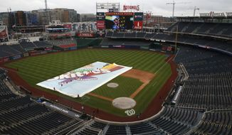 Members of the grounds crew removes the tarp ahead of a baseball game between the Washington Nationals against the Chicago Cubs, Thursday, Sept. 13, 2018, at Nationals Park in Washington. (AP Photo/Jacquelyn Martin)