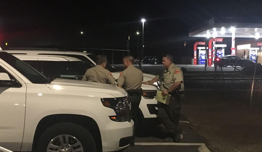 Kern County Sheriff's deputies gather near the scene, Wednesday, Sept. 12, 2018, in southeast Bakersfield, Calif., where authorities say a gunman killed multiple people. (Sam Morgen/The Bakersfield Californian via AP)