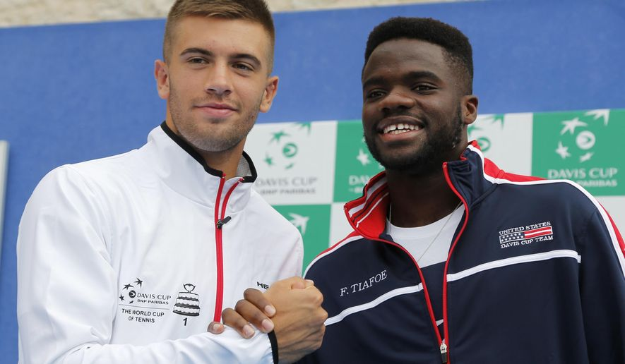 Croatia's Borna Coric, left and United States' Frances Tiafoe pose for cameras after the draw ahead of Davis Cup semifinal matches between Croatia and the United States in Zadar, Croatia, Thursday, Sept. 13, 2018. (AP Photo/Darko Bandic)