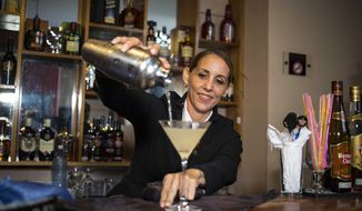 In this Aug. 27, 2018 photo, Cuban bartender Barbara Betancourt Bernal pours a daiquiri at a bar in Havana, Cuba. Known to friends and family as Barbarita, the 46-year-old's career spans two decades. (AP Photo/Desmond Boylan)