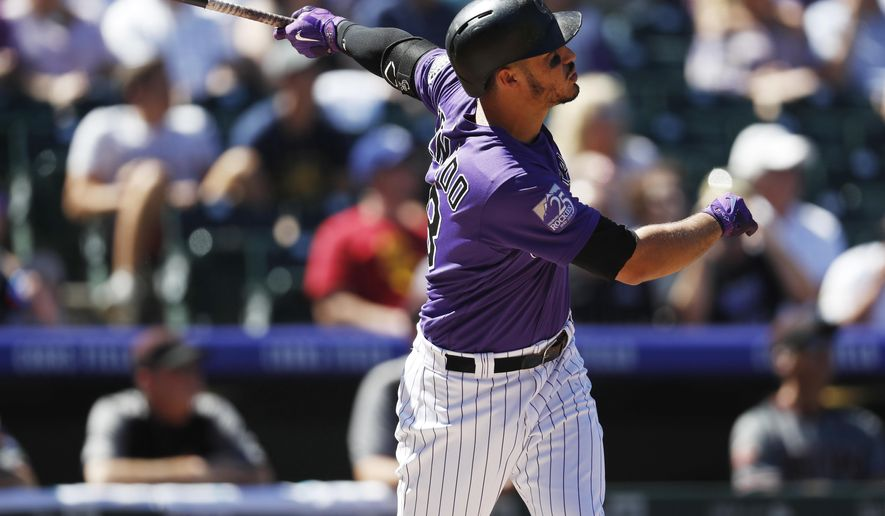 Colorado Rockies' Nolan Arenado follows the flight of his solo home run off Arizona Diamondbacks starting pitcher Matt Koch in the first inning of a baseball game Thursday, Sept. 13, 2018, in Denver. (AP Photo/David Zalubowski)