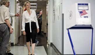 "Polling station officials direct New York gubernatorial candidate Cynthia Nixon to her voting area for the primary, Thursday, Sept. 13, 2018, in New York. Democrats across New York state are picking the winner of a long and sometimes nasty primary contest between Gov. Andrew Cuomo and activist and former ""Sex and the City"" star Nixon.  (AP Photo/Bebeto Matthews)"