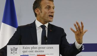 "French President Emmanuel Macron delivers a speech on poverty to social aid workers in Paris, France, Thursday, Sept. 13, 2018. French President Emmanuel Macron has unveiled a 8-billion euro plan focusing on education and getting the unemployed back to work in an effort to combat poverty. Placard reads ""make more for those who have less"". (AP Photo/Michel Euler, Pool)"