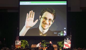 FILE - In this Feb. 14, 2015, file photo, Edward Snowden appears on a live video feed broadcast from Moscow at an event sponsored by ACLU Hawaii in Honolulu. Europe's human rights court is about to publish what could be a landmark ruling on the legality of mass surveillance. The case brought by civil liberties, human rights and journalism groups and campaigners challenges British surveillance and intelligence-sharing practices revealed by American whistleblower Edward Snowden. (AP Photo/Marco Garcia, File)