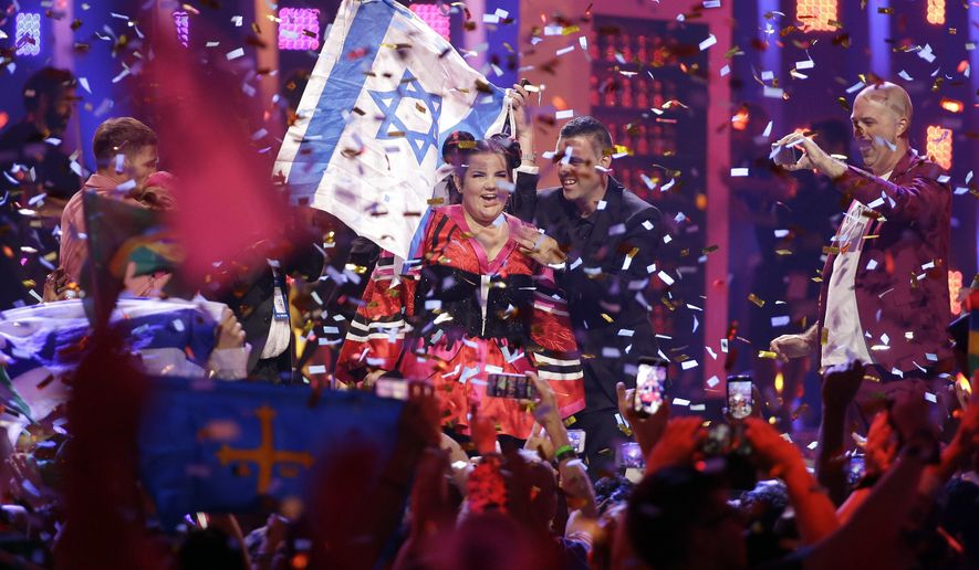 FILE - In this May 12, 2018 file photo, Netta Barzilai from Israel celebrates after winning the Eurovision song contest in Lisbon, Portugal. The Eurovision Song Contest has announced that next year's competition will be held in Tel Aviv. The government initially insisted on holding the popular event in Jerusalem. But following a backlash over the U.S. recognition of Jerusalem as its capital and a subsequent fear of boycotts it dropped the demand. (AP Photo/Armando Franca, File)