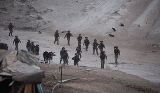Israeli security forces arrive to the West Bank Bedouin community of Khan al-Ahmar, Thursday, Sept. 13, 2018. Israeli forces have dismantled five corrugated metal shacks that had been set up by Palestinian activists protesting the anticipated razing of a nearby West Bank hamlet. Protest leader Abdullah Abu Rahmeh says about 200 soldiers converged on the area of the Khan al-Ahmar encampment before dawn Thursday, dismantled the shacks and loaded the parts onto trucks. (AP Photo/Majdi Mohammed)