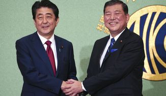 Candidates for the president of ruling party Liberal Democratic Party, Japanese Prime Minister and head of current party president Shinzo Abe, left, and Shigeru Ishiba shake hands prior to a debate ahead of Liberal Democratic Party president election in Tokyo Friday, Sept. 14, 2018. Abe is vying for his third re-election as the ruling party leader next week, extending his stay in power to work on his long-cherished ambition, to revise his country's war-renouncing constitution. (AP Photo/Eugene Hoshiko)