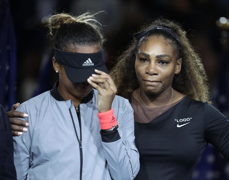 """FILE - In this Sept. 8, 2018, file photo, Naomi Osaka, of Japan, is hugged by Serena Williams after Osaka defeated Williams in the women's final of the U.S. Open tennis tournament, in New York. Naomi Osaka told television host Ellen DeGeneres that Serena Williams said she was """"proud"""" of her during the trophy ceremony while boos filled the stadium. Osaka appeared on """"The Ellen DeGeneres Show"""" Wednesday.(AP Photo/Julio Cortez)"""