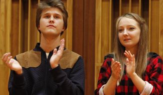 Aleksandra Swigut, right, applauds Tomasz Ritter, left, of Poland who is declared the winner of the 1st Chopin Competition on Period Instruments in Warsaw, Poland, Thursday, Sept. 13, 2018.  The announcement took place after each of the six finalists played a Chopin concerto accompanied by the Amsterdam-based Orchestra of the 18th century. (AP Photo/Czarek Sokolowski)