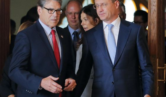 Russian Energy Minister Alexander Novak, right, welcomes U.S. Secretary of Energy Rick Perry for the talks in Moscow, Russia, Thursday, Sept. 13, 2018. (AP Photo/Alexander Zemlianichenko)