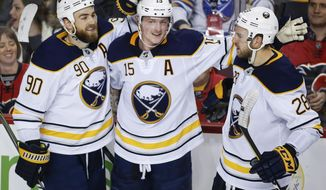 FILE - In this Jan. 22, 2018, file photo, Buffalo Sabres'  Jack Eichel, center, celebrates his game-winning goal during overtime of an NHL hockey game against the Calgary Flames, in Calgary. Eichel was in such an upbeat mood upon reporting for the start of training camp Thursday, Sept. 13, 2018, the Sabres star center managed to engage in some humorous banter with reporters. (Jeff McIntosh/The Canadian Press via AP, File)