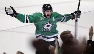 FILE - In this March 3, 2018, file photo, Dallas Stars' Tyler Seguin (91) celebrates their 3-2 overtime win in an NHL hockey game against the St. Louis Blues in Dallas. Seguin has signed a $78.8 million, eight-year contract extension with the Stars, general manager Jim Nill announced  Thursday, Sept. 13, 2018. (AP Photo/Tony Gutierrez, File)
