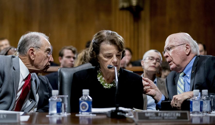 Senate Judiciary Committee Chairman Chuck Grassley, R-Iowa, left, accompanied by Sen. Dianne Feinstein, D-Calif., the ranking member, center, speaks with Sen. Patrick Leahy, D-Vt., right, during a Senate Judiciary Committee markup meeting on Capitol Hill, Thursday, Sept. 13, 2018, in Washington. The committee will vote next week on whether to recommend President Donald Trump's Supreme Court nominee, Brett Kavanaugh for confirmation. Republicans hope to confirm him to the court by Oct. 1.(AP Photo/Andrew Harnik)