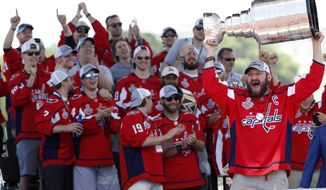 In this June 12, 2018, file photo, Washington Capitals' Alex Ovechkin, from Russia, right, holds up the Stanley Cup during a victory rally in Washington. (AP Photo/Jacquelyn Martin, File) ** FILE **