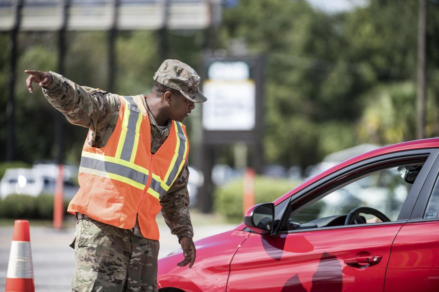 A National Guardsman directs traffic onto U.S. Highway 501 as Hurricane Florence approaches the East Coast Wednesday, Sept. 12, 2018, near Conway, S.C. Time is running short to get out of the way of Hurricane Florence, a monster of a storm that has a region of more than 10 million people in its potentially devastating sights. (AP Photo/Sean Rayford)