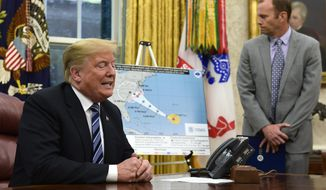 President Donald Trump, left, talks about Hurricane Florence during a briefing in the Oval Office of the White House in Washington, Tuesday, Sept. 11, 2018, as FEMA Administrator Brock Long listens at right. (AP Photo/Susan Walsh)