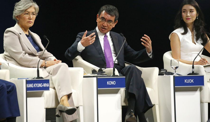 Japanese Foreign Minister Taro Kono, center, gestures talks about Asia's Geopolitcal Outlook in the ongoing World Economic Forum on ASEAN at the National Convention Center Thursday, Sept. 13, 2018 in Hanoi, Vietnam. Listening at left is South Korean Foreign Minister Kang Kyung-wha and Lynn Kuok, International Institute of Strategic Studies, Singapore. The World Economic Forum has attracted hundreds of participants with the theme: ASEAN 4.0: Entrepreneurship and the Fourth Industrial Revolution. (AP Photo/Bullit Marquez)