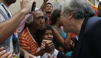 Organization of American States Secretary-General Luis Almagro greets Venezuelan migrants in La Parada, Colombia, Friday, Sept. 14, 2018. Almagro traveled to the Colombia's border with Venezuela to monitor the situation of migrants who have been fleeing the socialist-run country amid hyperinflation and widespread shortages and widespread shortages. (AP Photo/Fernando Vergara)