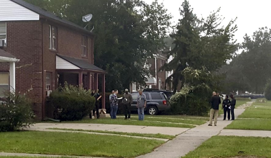 Police gather at a Detroit home where a man was shot and killed early Friday, Sept. 14, 2018, by police during the execution of a search warrant in connection with the death of a 5-year-old girl.  (Leonard Fleming /Detroit News via AP)