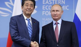 FILE - In this Sept. 10, 2018, file photo, Japanese Prime Minister Shinzo Abe, left, and Russian President Vladimir Putin shake hands prior to their talks at the Eastern Economic Forum in Vladivostok, Russia. Abe says he will meet again this year for more talks with Putin on Putin's proposal for the two countries to sign a peace treaty and discuss the status of disputed islands. (Mikhail Metzel/TASS News Agency Pool Photo via AP, FIle)