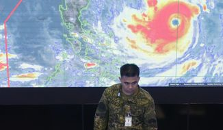 A member of the Philippine Air Force stands in front of a satellite image of Typhoon Mangkhut, locally named Typhoon Ompong, at the National Disaster Risk Reduction and Management Council operations center in metropolitan Manila, Philippines on Thursday, Sept. 13, 2018. Philippine officials have begun evacuating thousands of people in the path of the most powerful typhoon this year, closing schools and readying bulldozers for landslides. (AP Photo/Aaron Favila)