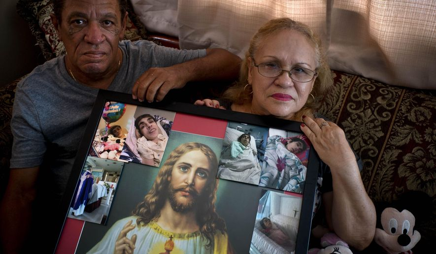 In this Sept. 4, 2018 photo, Maria Gonzalez Munoz, right, and Juan Manuel Gonzalez, pose with an image of Jesus surrounded by photos of her sister Ramona, when she was sick and during her funeral, in San Juan, Puerto Rico. Ramona, a disabled, 59-year-old who suffered from a degenerative brain disease, did not drown when Hurricane Maria drenched Puerto Rico, but instead she died a month later from sepsis, caused, says her family, by an untreated bedsore. Maria spent 30 days after the storm caring for her sister in her blacked-out home. (AP Photo/Ramon Espinosa)