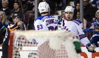 FILE - In this Feb. 28, 2018, file phot, New York Rangers' Chris Kreider, back right, and Mika Zibanejad, of Sweden, celebrate Zibanejad's goal against the Vancouver Canucks during the third period of an NHL hockey game in Vancouver, British Columbia. Kreider and the New York Rangers have put last season's struggles behind and are just focusing on the future. The Rangers are in a rebuilding mode after dealing several stars in a youth movement at the trade deadline last winter and then finishing 20 points out of a playoff spot.  (Darryl Dyck/The Canadian Press via AP)