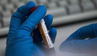 FILE - In this May 24, 2016 file photo an employee of the Russia's national drug-testing laboratory holds a vial in Moscow, Russia. In what appears to be a sudden change of positions, a key review committee is recommending Russia's anti-doping agency be reinstated after a nearly three-year suspension resulting from the country's scheme to circumvent rules and win Olympic medals. (AP Photo/Alexander Zemlianichenko, File)