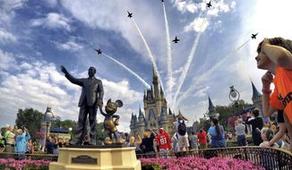 """In this April 16, 2017, file photo, the Blue Angels, the U.S. Navy's legendary flight performance squadron, fly in formation over Cinderella Castle and the """"Partners"""" statue at the Magic Kingdom at Walt Disney World, in Bay Lake, Fla. (Joe Burbank/Orlando Sentinel via AP, File)"""