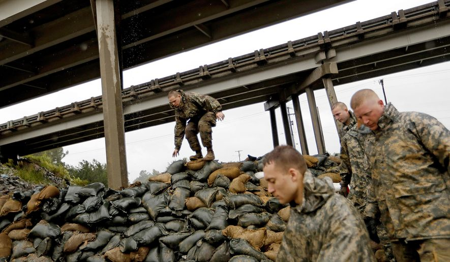 Members of the North Carolina National Guard finish stacking sand bags under a highway overpass near the Lumber River which is expected to flood from Hurricane Florence's rain in Lumberton, N.C., Friday, Sept. 14, 2018. (AP Photo/David Goldman)