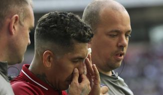 Liverpool's Roberto Firmino, holds a patch over his eye after he received a treatment during the English Premier League soccer match between Tottenham Hotspur and Liverpool at Wembley Stadium in London, Saturday Sept. 15, 2018. (AP Photo/Tim Ireland)