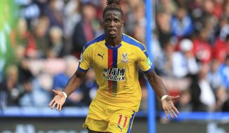 Crystal Palace's Wilfried Zaha celebrates scoring his side's first goal of the game during the English Premier League soccer match between Huddersfield and Crystal Palace, at the Kirklees Stadium, in Huddersfield, England, Saturday Sept. 15, 2018. (Mike Egerton/PA via AP)