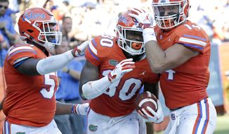 Florida safety Amari Burney (30) celebrates with linebacker Ventrell Miller, left, and tight end Lucas Kull, right, after he blocked a Colorado State punt that led to a Florida touchdown during the first half of an NCAA college football game, Saturday, Sept. 15, 2018, in Gainesville, Fla. (AP Photo/John Raoux)